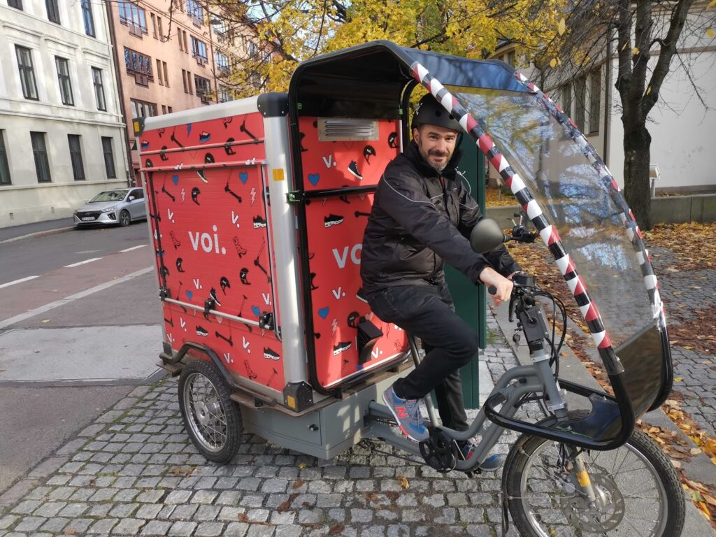 a man on an electric cargo bike branded with voi logos