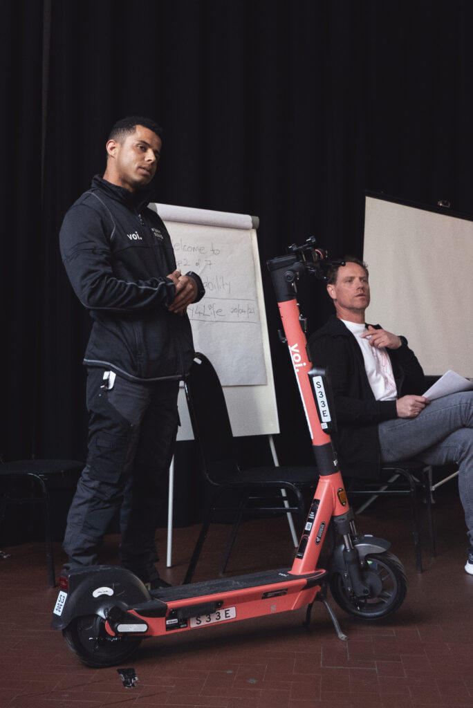 Two men next to a scooter giving a talk