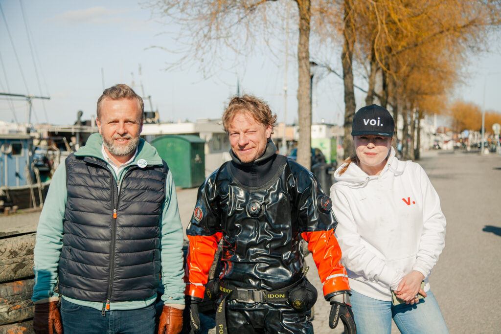 Voi's VP Comms Kristina Hunter Nilsson together with a diver and Fredrik Johansson, the founder of Rena Mälaren.