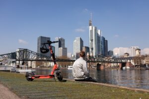 Person sitting at Main river in Frankfurt with Voi scooter