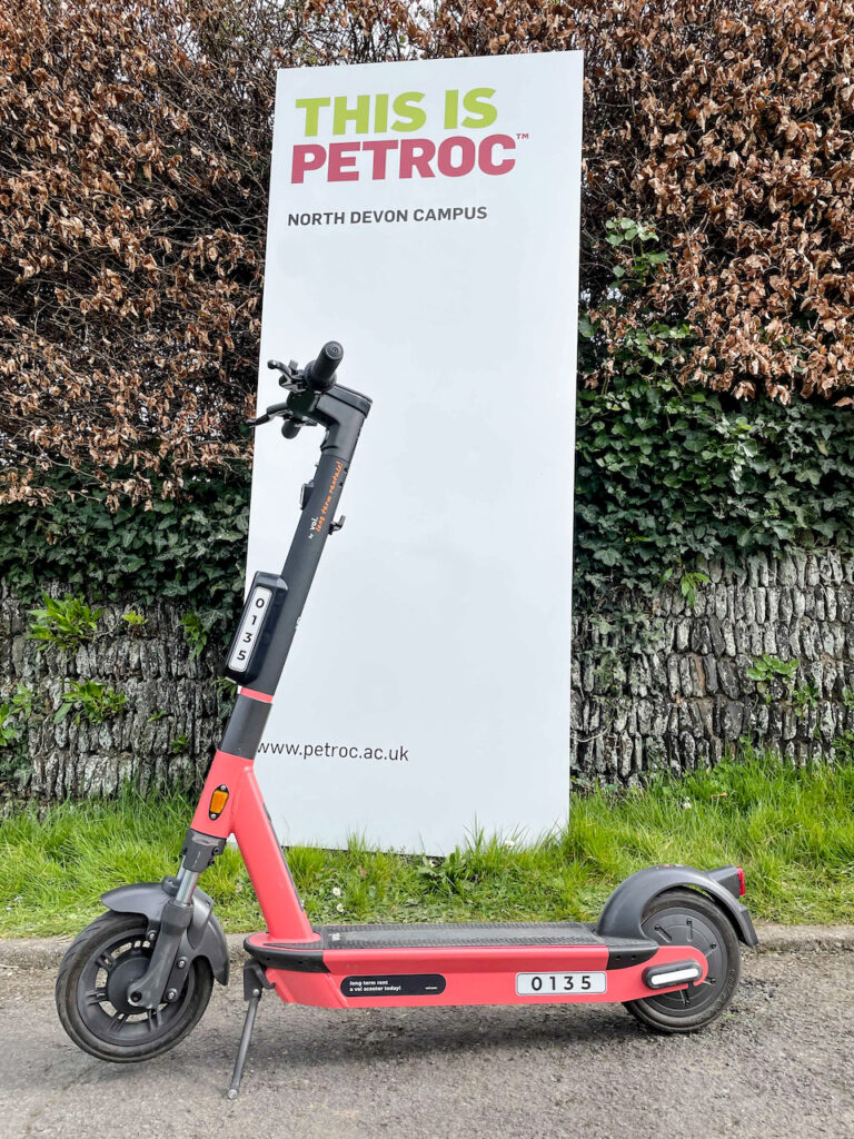 An e-scooter is parked in front of a billboard