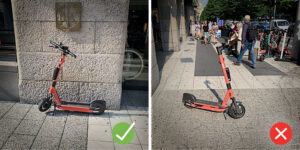 One scooter parked properly next to a wall, another misplaced on the pavement.