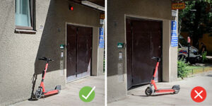 One scooter parked properly next a wall, another misplaced in front of an entrance.