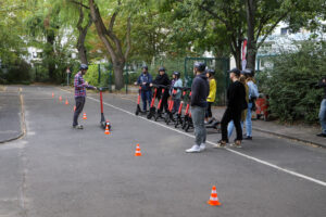 male instructor standing in front of a group of students holding red e-scooters next to a safety track