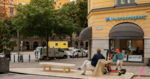 wooden parklet with parking space for micromobility as well as a social area with seating and a table